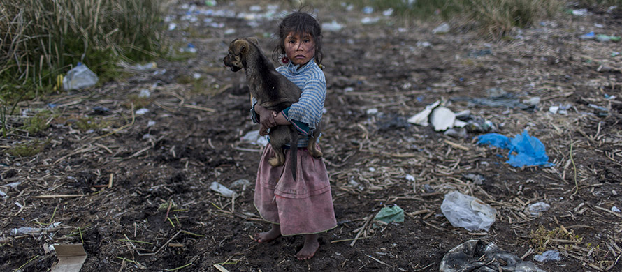 Melinda Quispe walks on the trash strewn shore of Lake Titicaca, as she holds her dog, in her village Kapi Cruz Grande, in the Puno region of Peru. (AP Photo/Rodrigo Abd)