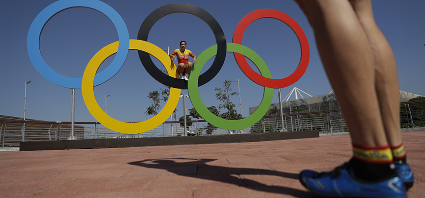 Spanish cyclist Tania Calvo poses for a picture for her teammate Juan Peralta on the Olympics rings in the Olympic Park ahead of the 2016 Summer Olympics in Rio de Janeiro, Brazil, Monday, Aug. 1, 2016. (AP Photo/Matt Dunham)
