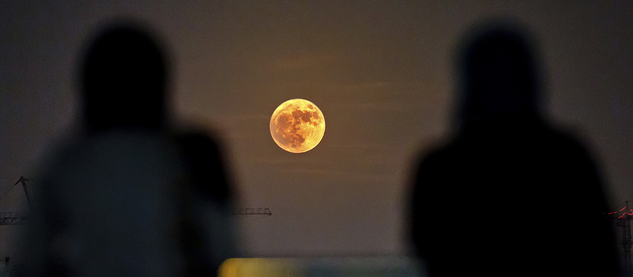 "Two Iranian women watch the ""Supermoon"" rising over Tehran in Iran. (AP Photo/Ebrahim Noroozi)"