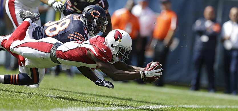 Arizona Cardinals wide receiver Jaron Brown (13) dives into the end zone for a touchdown against Chicago Bears safety Adrian Amos (38) during the first half of an NFL football game , Sunday, Sept. 20, 2015, in Chicago. (AP Photo/Michael Conroy)