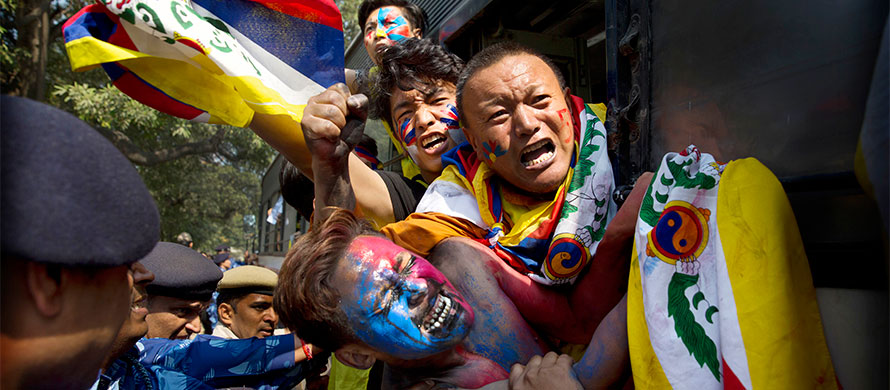 Indian para-military force soldiers push exiled Tibetan activists into a police bus during a protest outside the Chinese Embassy, in New Delhi, India, Friday, March 9, 2018. (AP Photo/Manish Swarup)