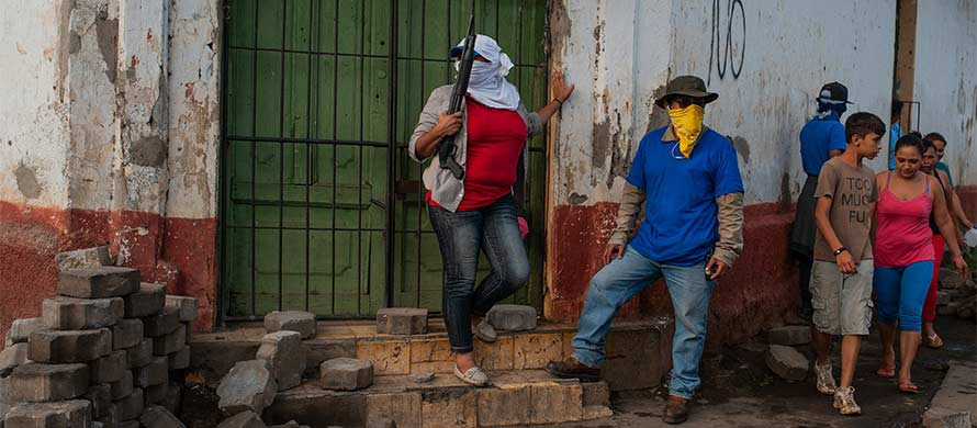 Sandinista militias stand guard at a torn down barricade after police and pro-government militias stormed the Monimbo neighborhood of Masaya, Nicaragua, Tuesday, July 17, 2018. (AP Photo/Cristibal Venegas)