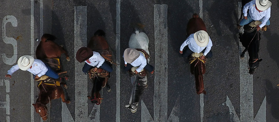 Men ride horses down Paseo de la Reforma during a parade marking the 109th anniversary of the start of the Mexican Revolution, in Mexico City, Wednesday, Nov. 20, 2019. (AP Photo/Rebecca Blackwell)