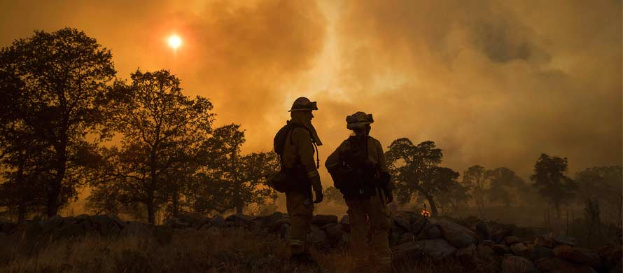 CalFire firefighter Jake Hainey, left, and engineer Anna Mathiasen watch as a wildfire burns near Oroville, Calif., on Saturday, July 8, 2017. (AP Photo/Noah Berger)